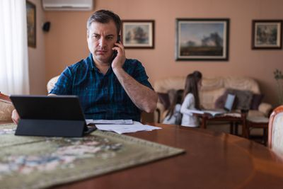 Man frowning while having telephone conversation at desk with laptop.