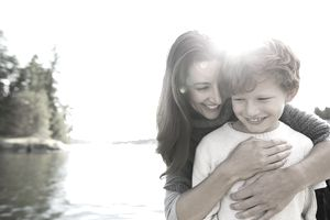 Mother hugging son at sunny lakeside