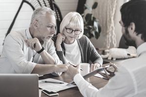 Financial advisor explaining paperwork to a couple on tablet at a desk