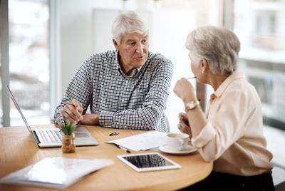 Retired couple talking about financial matters at a home table with a laptop