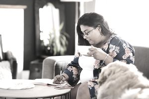 A person drinks coffee while writing in a journal.