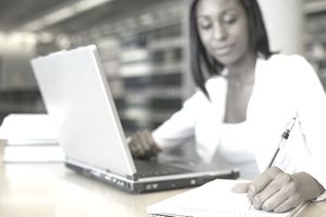 a young woman taking notes while sitting in front of a laptop
