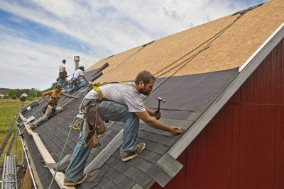 Workers install roof on rural home under construction