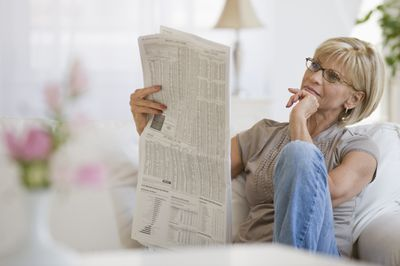 Woman reading stock tables in a newspaper in living room