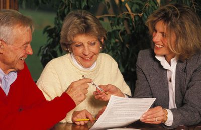 Older couple signing papers with younger attorney