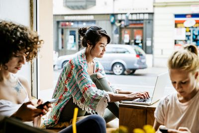 A stylish young woman is working from a busy cafe, sat by the window using her laptop.