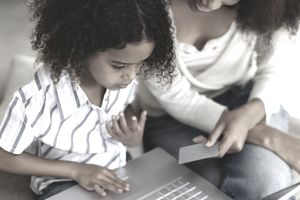 Mother and her daughter using a laptop for home shopping