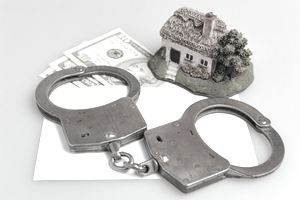 Handcuffs sitting on a piece of paper next to a small house figurine and $10 bills