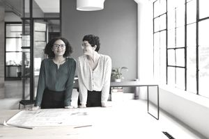 Two businesswomen with blueprints on desk in bright office