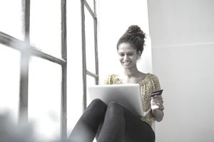 Woman sitting on window sill with laptop and credit card