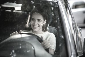 Young happy woman driving a car.