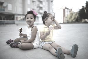 "Two little girls sit on the sidewalk and enjoy melting ice cream novelties on a hot day. One of them appears to be experiencing ""brainfreeze."""