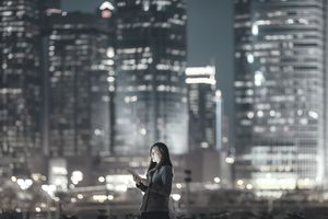 Woman using tablet in financial district in international city