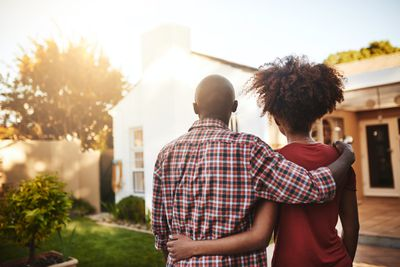 A couple standing outside looking at a house with their arms around each other