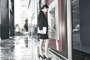businesswoman using ATM in city