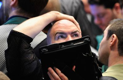 Trader in a sideways market holds his head as he looks at movement on the big board