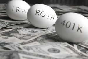 "Eggs with gold letters spelling ""IRA"" ""ROTH"" and ""401k"" on a pile of money."