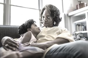 Grandmother and granddaughter cuddling on couch