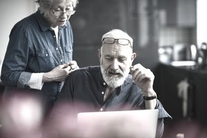 Candid portrait of senior couple at home, man with grey hair and beard working on computer