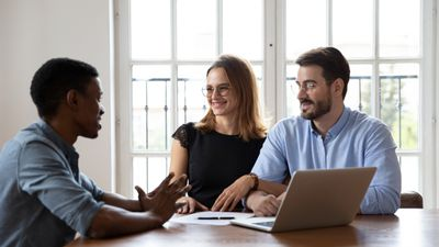 Mortgage banker consulting with client couple in a meeting