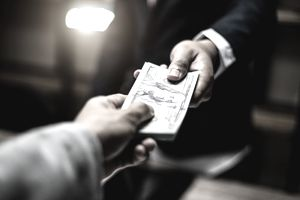 A person in a suit hands a wad of US $100 bills to another person