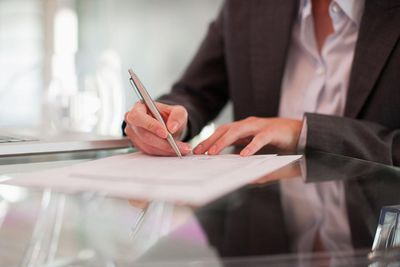 Woman dressed in business jacket with pen in hand, making changes to her will at desk