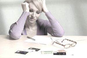 Woman looking stressed as she views credit card statement with several cards laying nearby