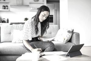 Woman analyzing documents while sitting at home.