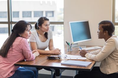 Female loan officer talks with young woman and her mom about obtaining a student loan.
