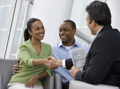 Smiling couple shake hands with banker holding papers