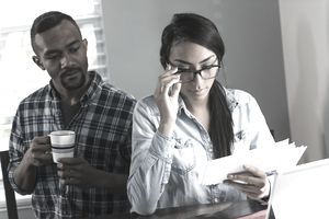 Woman looking at letters at home while man stands behind her.