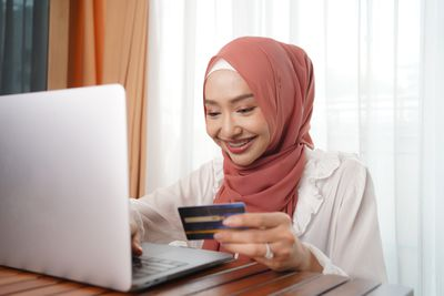 A smiling woman holding a credit card uses a laptop.