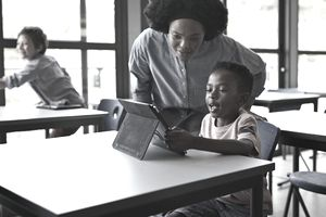 A teacher leans in to help a young student navigate a tablet computer screen.