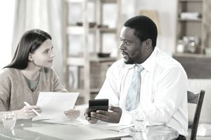 Adult black man and young white woman sitting at table and talking with papers