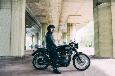 A man sits on his motorcycle under a bridge