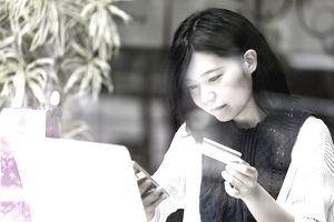 Young woman looking at smartphone and laptop while holding credit card