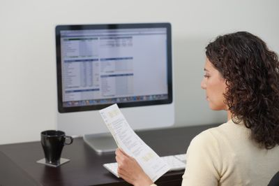 a woman sitting at a desk in front of a computer holding a document