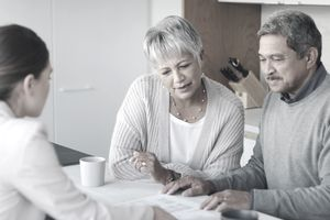 A couple meeting with a consultant to discuss paperwork at home