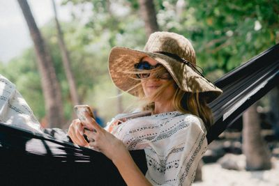 Woman laying in a hammock checking her investments on her smartphone.