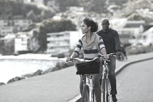 a man and woman riding bicycles on a path next to a town