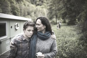 Mother consoles sad son as the walk outdoors