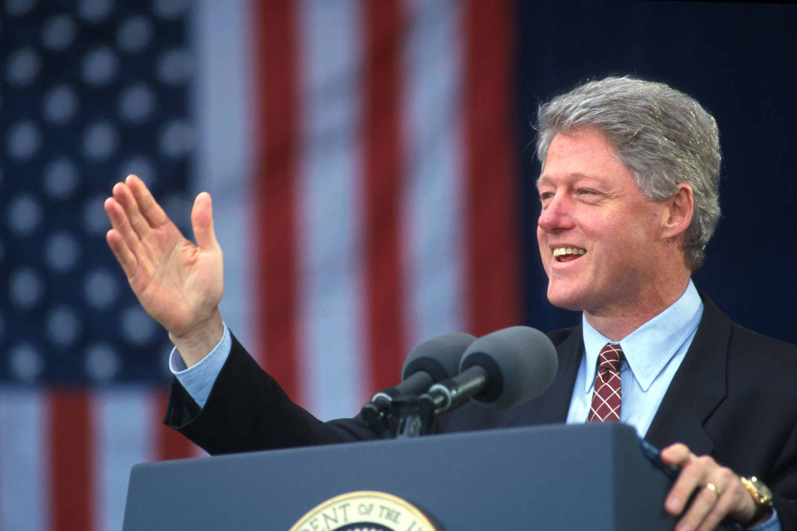 President Bill Clinton giving a speech in front of an American flag, 1995
