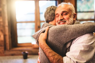 retirees having a hug and smiling