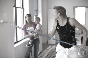 man painting inside home while woman and child look on