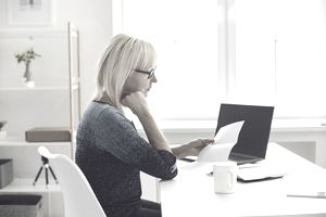 Blond woman in blue abrash sweater reviews papers at a desk near a laptop