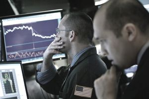 Day traders watching the stock market on screens.