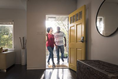 a couple walking into the entryway of their new home with big smiles on their faces