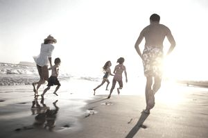 A family running on a beach at sunset