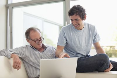 Adult son smiling and pointing to a laptop screen with his father