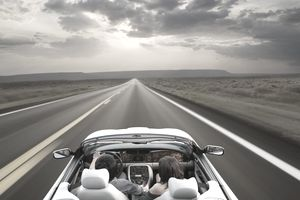Couple driving convertible through remote area
